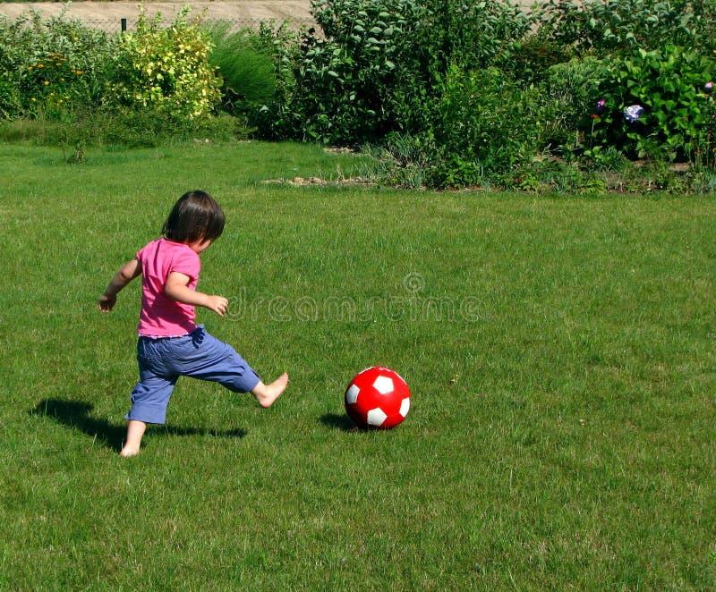 Jonge meisjes speelvoetbal in de tuin stock afbeeldingen