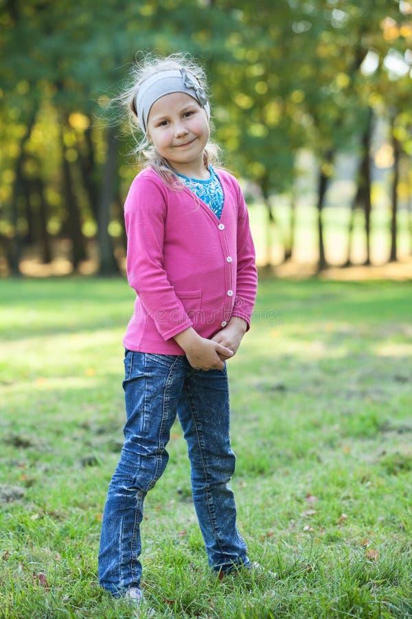 Jonge meisjes volledige lengte die zich op groen gras in park bevinden stock foto