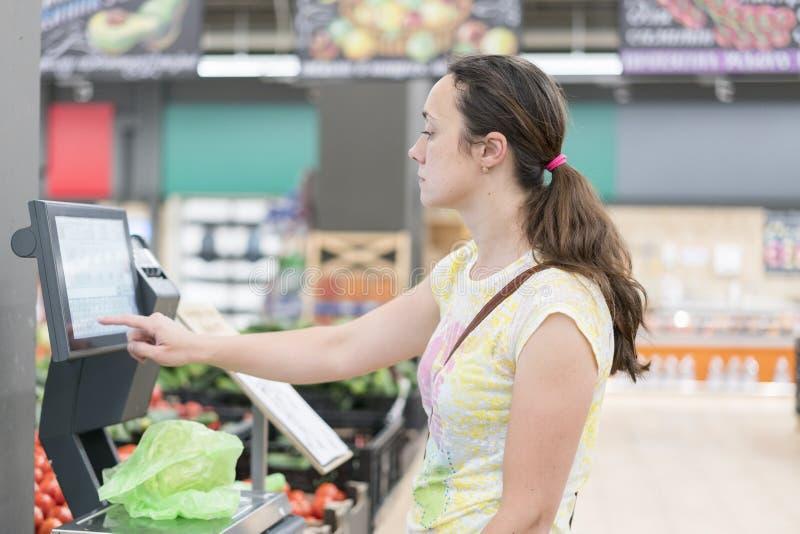 Jonge meisjes wegende banaan in supermarkt Het winkelen Vrouw die banaanvruchten biovoedsel in plantaardige opslag of supermarkt  stock afbeeldingen