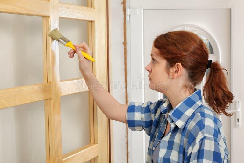 Jonge meisjesarbeider, die nieuwe houten deur schilderen royalty-vrije stock fotografie