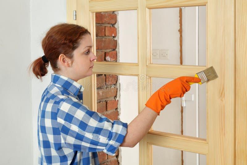 Jonge meisjesarbeider, die nieuwe houten deur schilderen stock fotografie