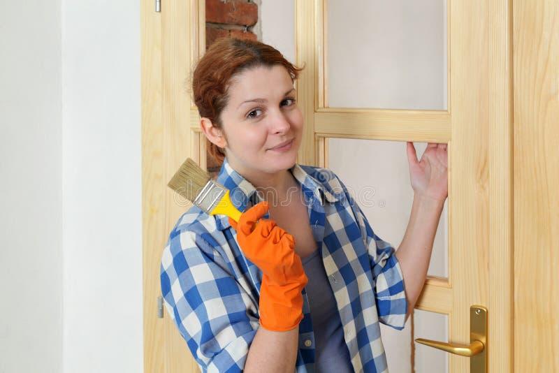 Jonge meisjesarbeider, die nieuwe houten deur schilderen royalty-vrije stock afbeeldingen