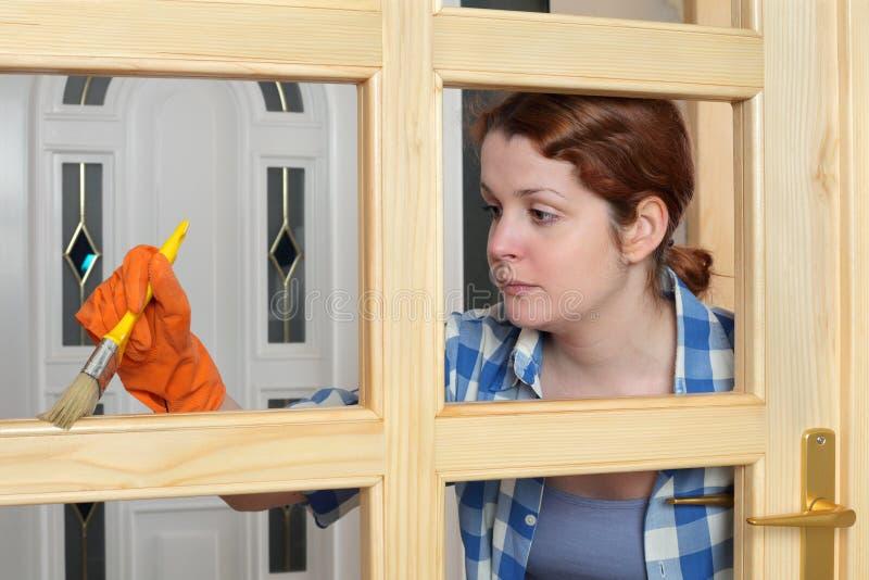 Jonge meisjesarbeider, die nieuwe houten deur schilderen stock afbeeldingen