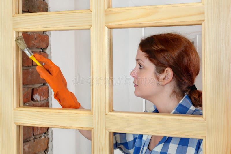 Jonge meisjesarbeider, die nieuwe houten deur schilderen stock foto