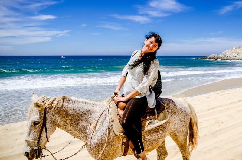 Jonge meisjeshorseback die op het strand in Cabo San Lucas, Baja California berijden royalty-vrije stock foto's