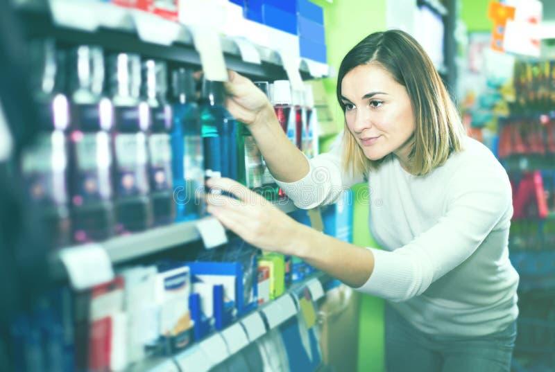 Jonge meisjesklant die efficiënte mondspoeling in supermark zoeken stock foto's