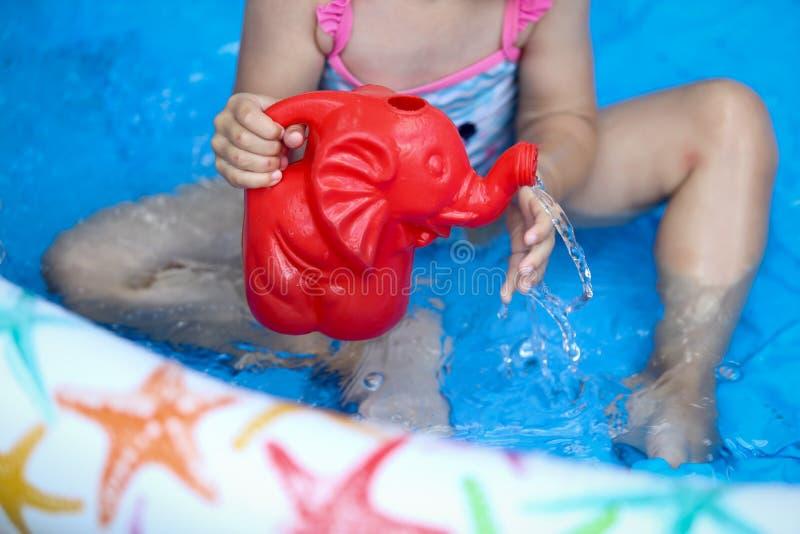 Jonge meisjesspelen met een plastic olifant in een opblaasbare swimmi stock afbeeldingen