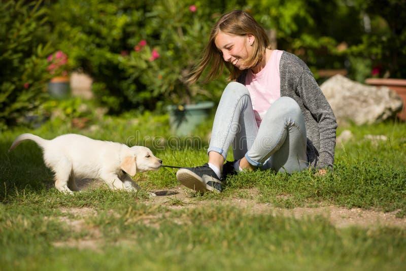 Jonge meisjesspelen met een zeer jonge hond van het golden retrieverpuppy in tuin Het kleine huisdier trekt haar schoenveter royalty-vrije stock afbeeldingen
