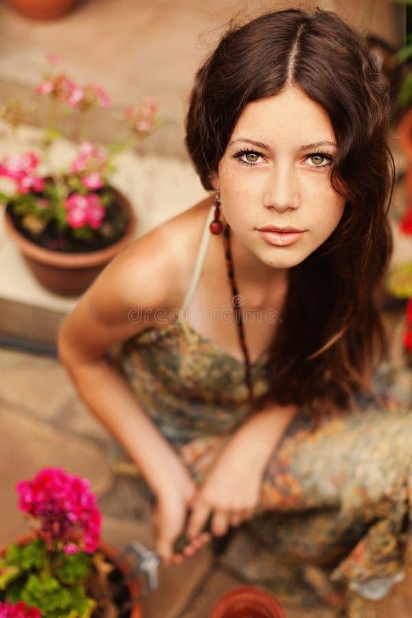 Jonge meisjestuinman die met lang bruin haar een tuinhulpmiddel houden royalty-vrije stock afbeeldingen