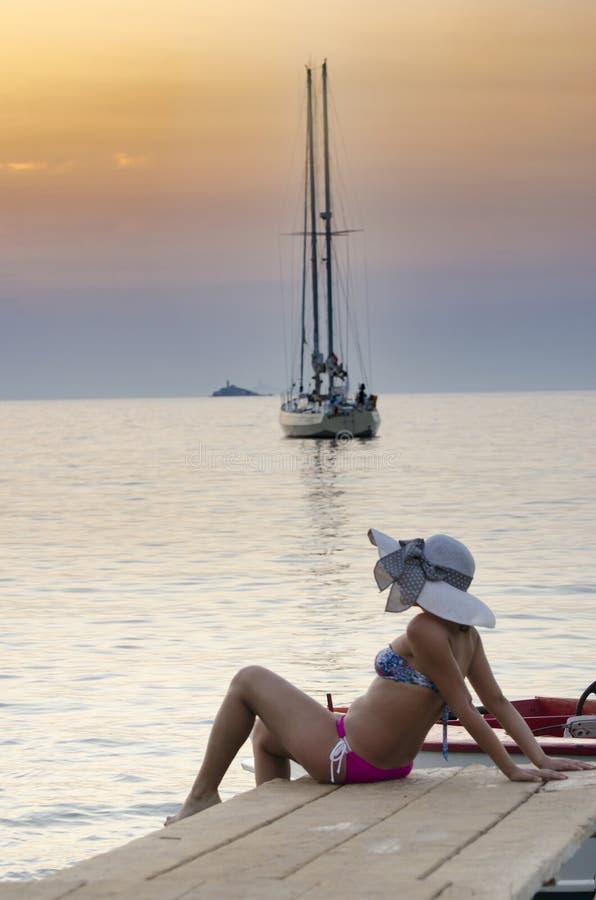 Jonge meisjesvrouw in bikini met hoedenzitting bij houten pijler en het kijken op de overzeese zonsondergang stock foto's