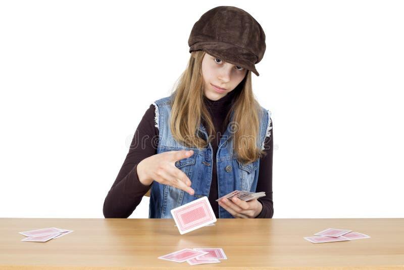 Jonge Meisjeszitting bij een Houten Lijst en Transactiespeelkaarten voor de Volgende die Ronde, op Wit wordt geïsoleerd stock foto