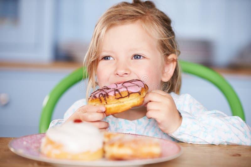 Jonge Meisjeszitting bij Lijst die Bevroren Doughnut eten royalty-vrije stock foto