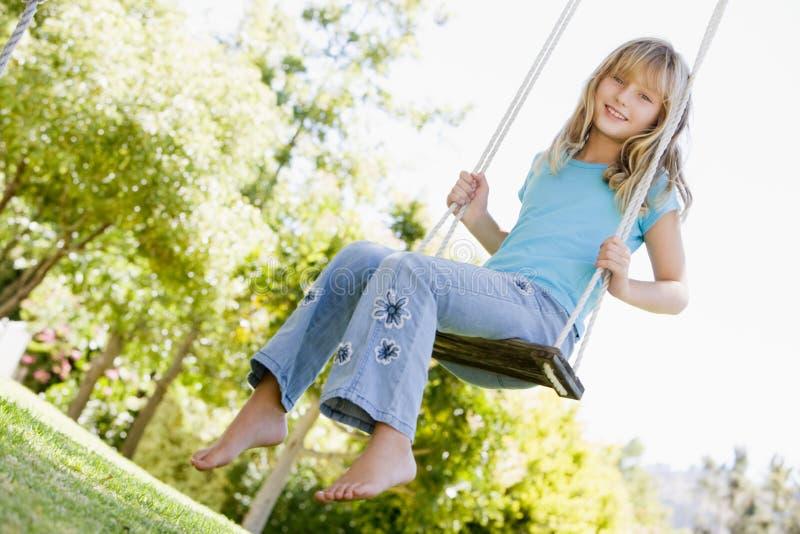Jonge meisjeszitting bij schommeling het glimlachen royalty-vrije stock afbeeldingen