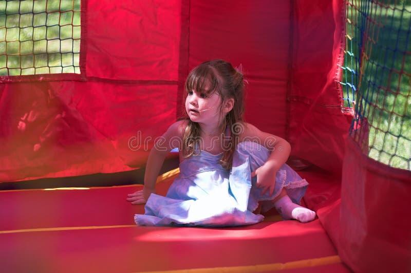 Jonge meisjeszitting in een opblaasbare bouncy stock afbeelding