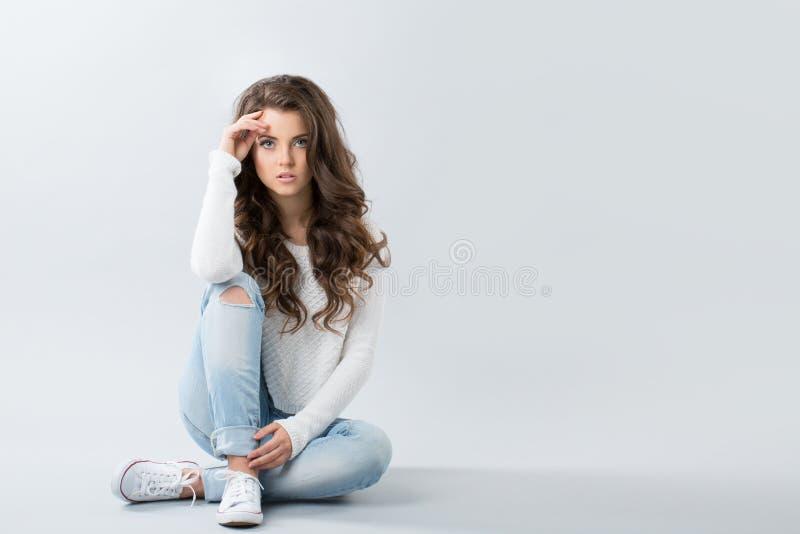 Jonge meisjeszitting in jeans en tennisschoenen stock foto