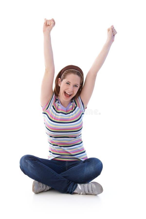 Jonge meisjeszitting in kleermakerszetel die gelukkig schreeuwt royalty-vrije stock foto