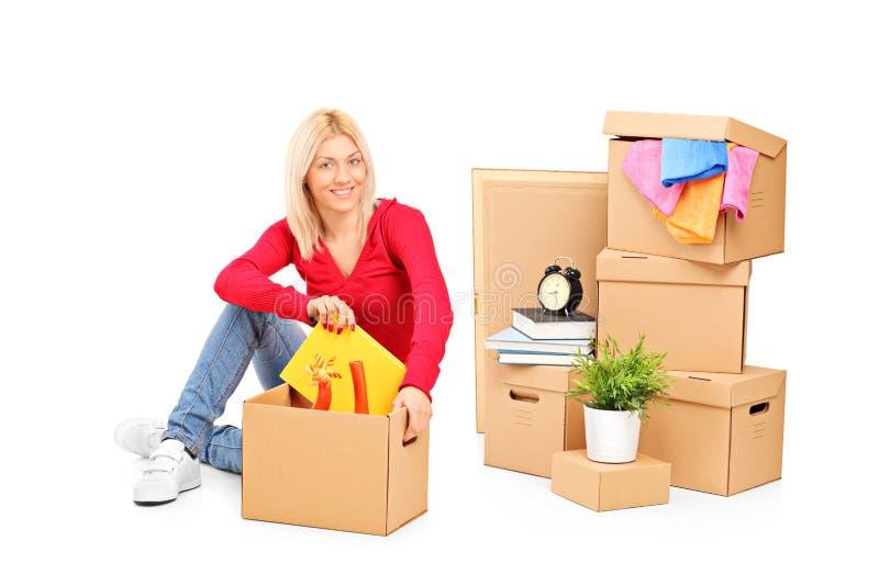 Jonge meisjeszitting met het bewegen van dozen naast haar stock afbeelding