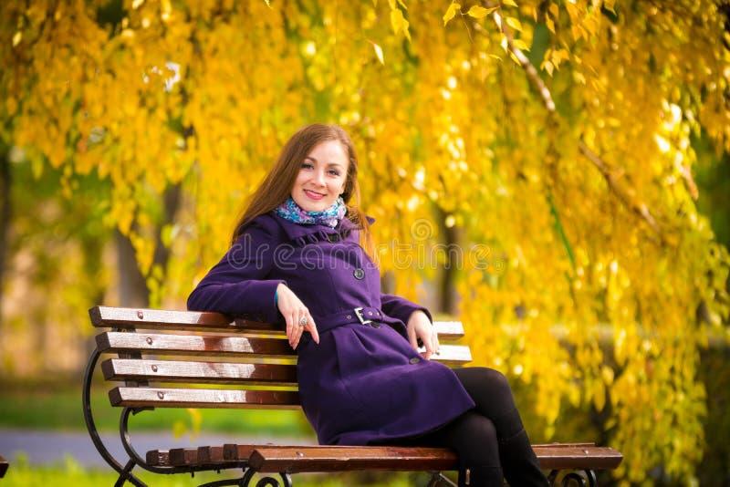 Jonge meisjeszitting op dag van de bank de warme herfst stock foto