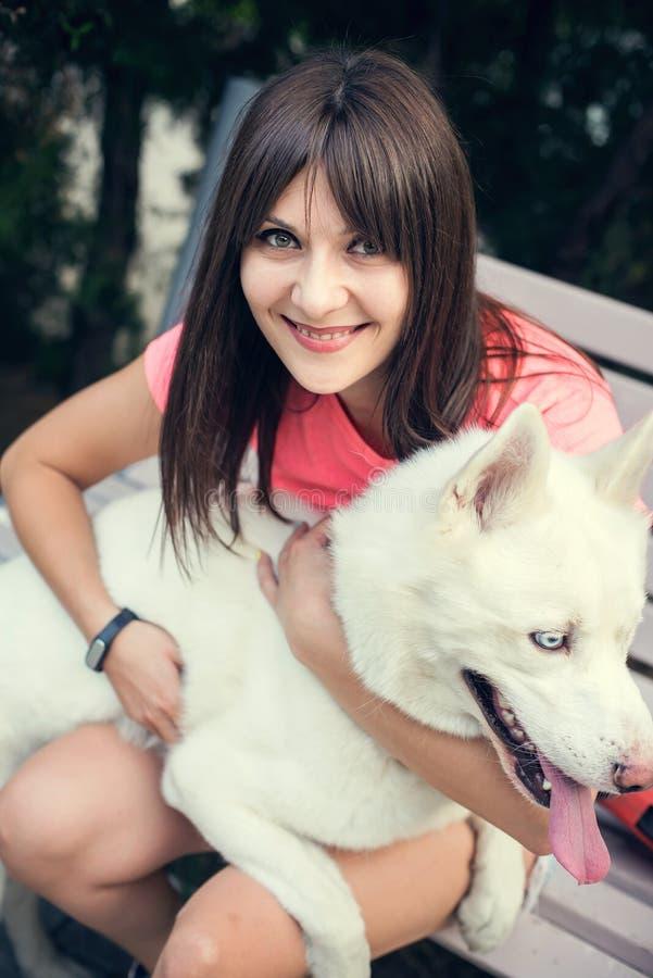 Jonge meisjeszitting op de bank en het spelen met haar witte schor hond stock foto's