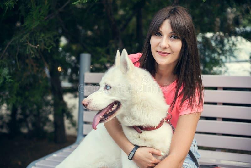 Jonge meisjeszitting op de bank en het spelen met haar witte schor hond royalty-vrije stock foto's