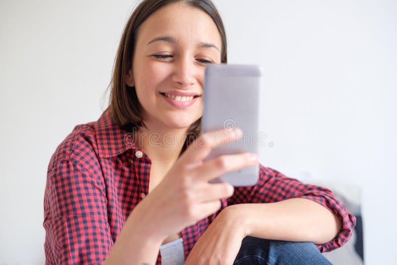 Jonge meisjeszitting op de bed en het letten op inhoud op slimme phon stock afbeelding