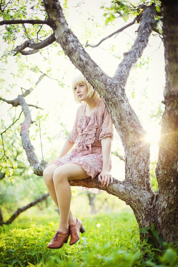 Jonge meisjeszitting op de boom royalty-vrije stock afbeeldingen