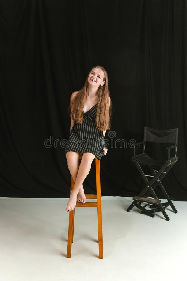 Jonge meisjeszitting op de hoge stoel op zwart-witte studioachtergrond stock afbeeldingen