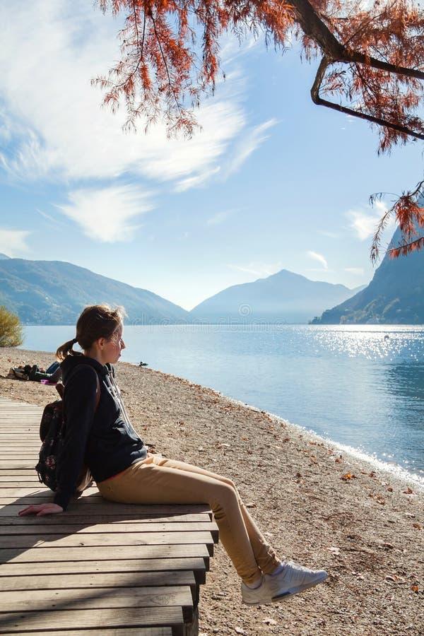 Jonge meisjeszitting op de meerkust in het de herfstpark Lugano stock foto