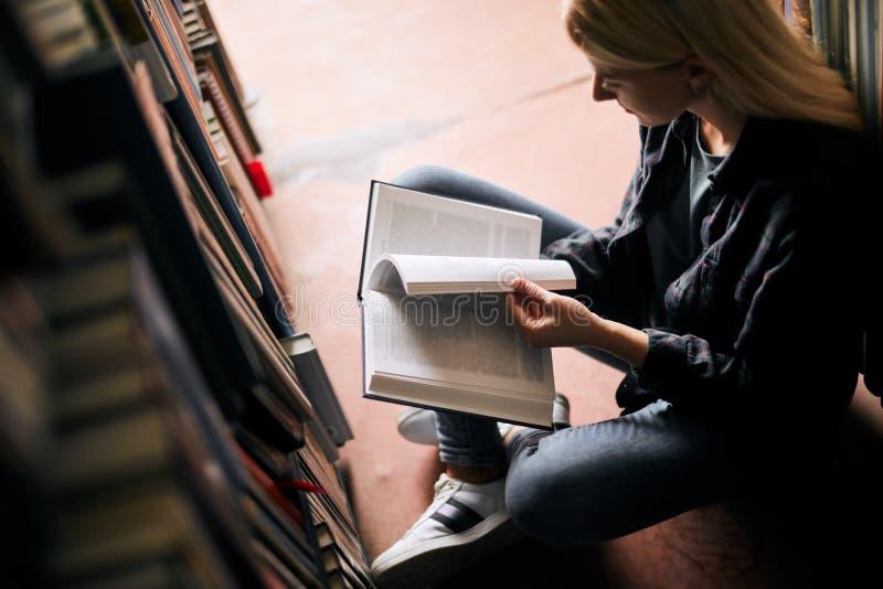 Jonge meisjeszitting op de vloer in bibliotheek tussen boekenrekken, lezingsboeken royalty-vrije stock foto