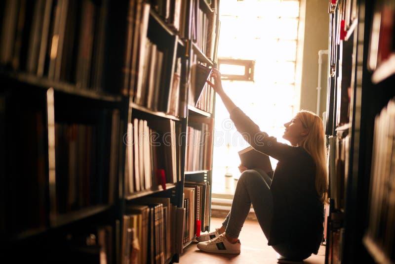 Jonge meisjeszitting op de vloer in traditionele bibliotheek bij boekenrekken, lezingsboeken Glimlachende en lachende student stock foto's