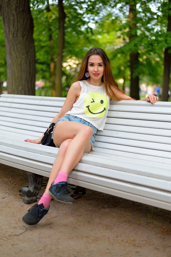Jonge meisjeszitting op een bank in Alexander Park stock fotografie