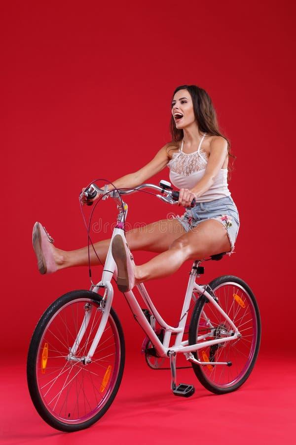 Jonge meisjeszitting op een fiets die haar benen, op een rode achtergrond opheffen stock afbeeldingen