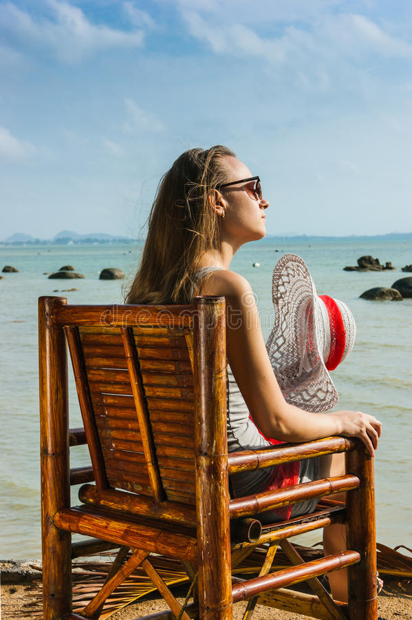 Jonge meisjeszitting op een stoel dichtbij het overzees stock foto