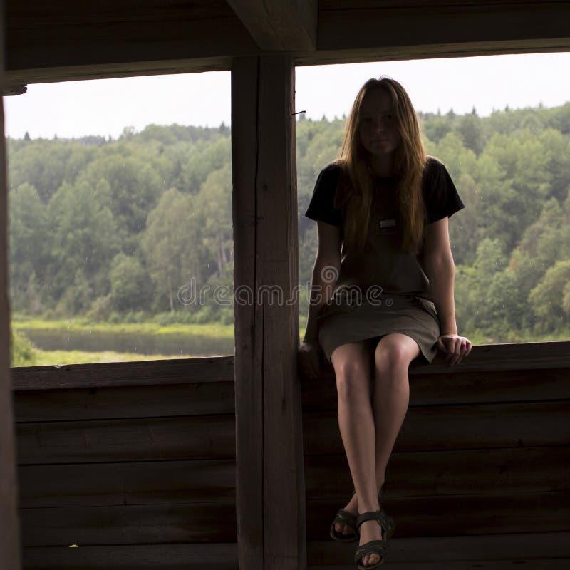 Jonge meisjeszitting op het traliewerk van een houten gazebo royalty-vrije stock afbeeldingen