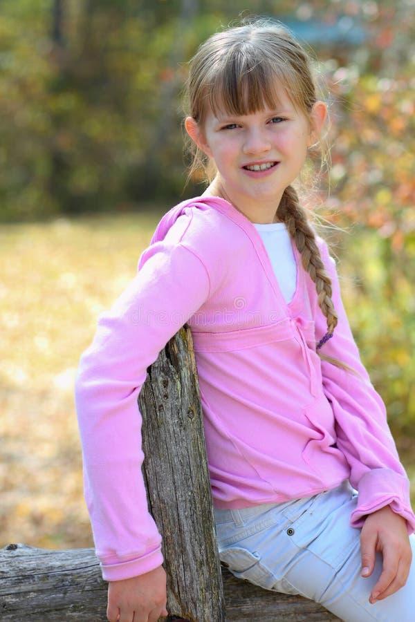Jonge meisjeszitting op omheining stock afbeeldingen