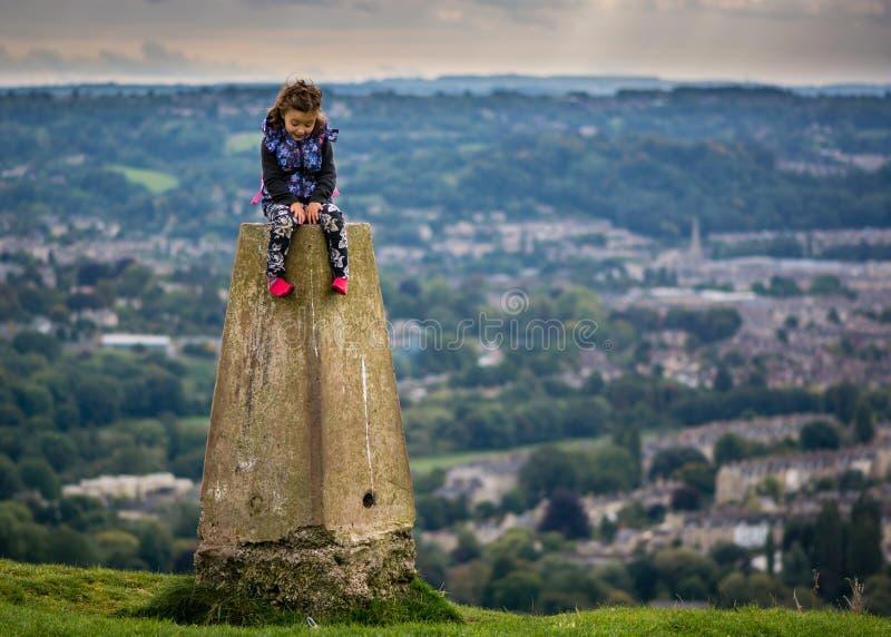 Jonge meisjeszitting op trianguleringspunt op Weinig Solsbury-Heuvel, die de Stad van de Werelderfenis van Bad, Somerset, het UK  royalty-vrije stock fotografie