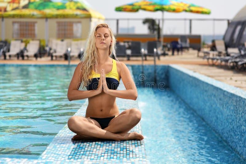 Jonge meisjeszitting in openlucht door de pool en het doen van oefeningen van royalty-vrije stock foto's