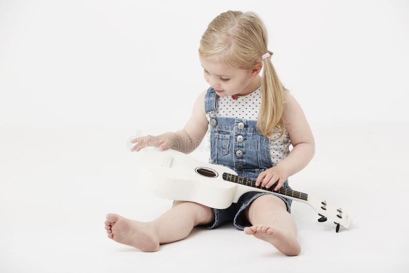 Jonge meisjeszitting in studio, die een gitaar spelen royalty-vrije stock fotografie