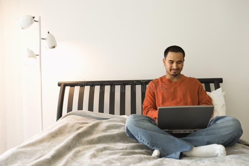 Jonge Mens in Bed dat Laptop met behulp van royalty-vrije stock fotografie