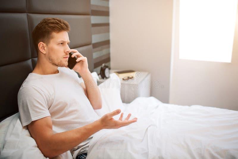 Jonge mens in bed vanochtend Het ernstige mannelijke model zit bij bed in ruimte en de bespreking op telefoon Hij behandelde met  royalty-vrije stock foto