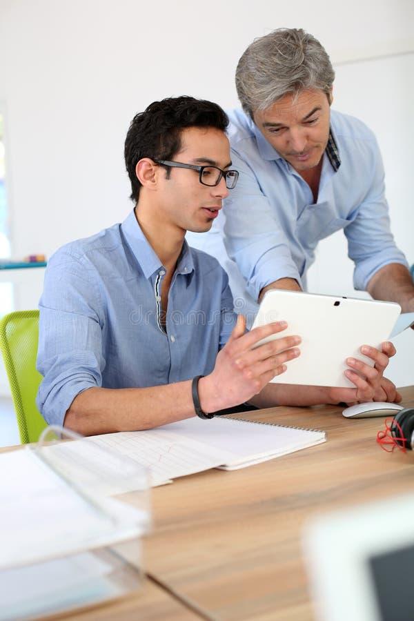 Jonge mens in bedrijfs opleiding met professor die tablet gebruiken royalty-vrije stock foto
