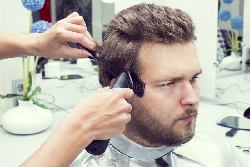 Jonge mens bij de kapper stock afbeeldingen