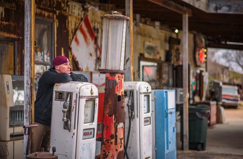Jonge mens bij een uitstekende benzinepomp stock afbeelding
