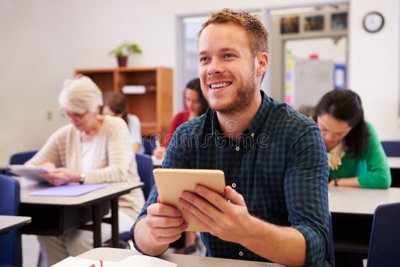 Jonge mens bij een volwassenenvormingsklasse die omhoog raad bekijken royalty-vrije stock foto's
