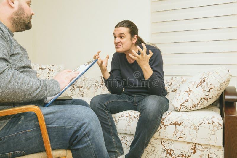 Jonge mens bij het psychotherapist bezoek, die over zijn problemen met emoties, geestelijk gezondheidsconcept spreken stock foto