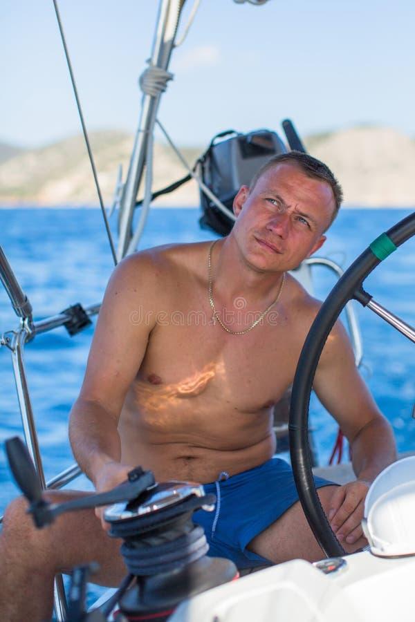 Jonge mens bij het roer van een varende jachtboot Sport royalty-vrije stock foto