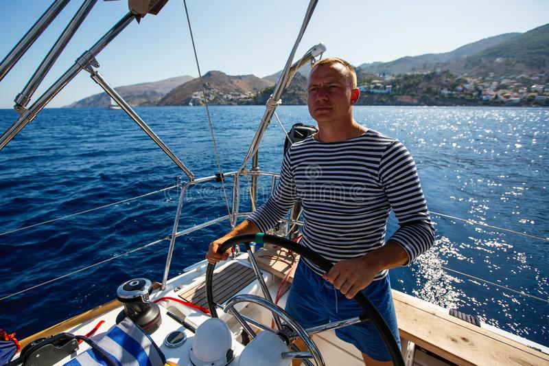 Jonge mens bij het roer van een varende jachtboot Sport royalty-vrije stock foto's