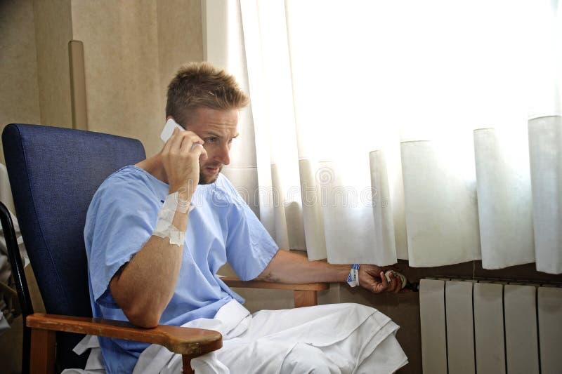 Jonge mens bij het ziekenhuisruimte die geduldige pyjama's dragen die door het venster zitten die op mobiele telefoon spreken stock foto's
