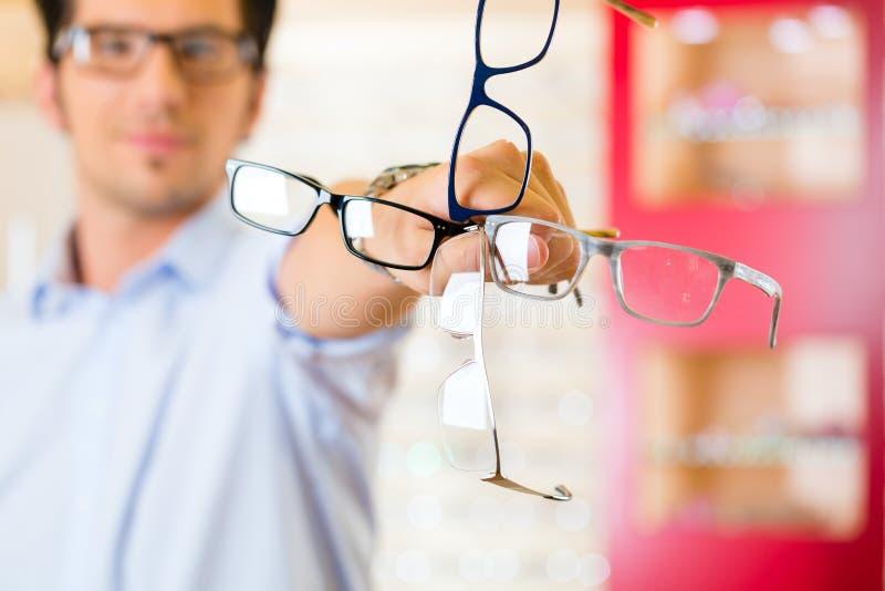 Jonge mens bij opticien met glazen stock afbeelding