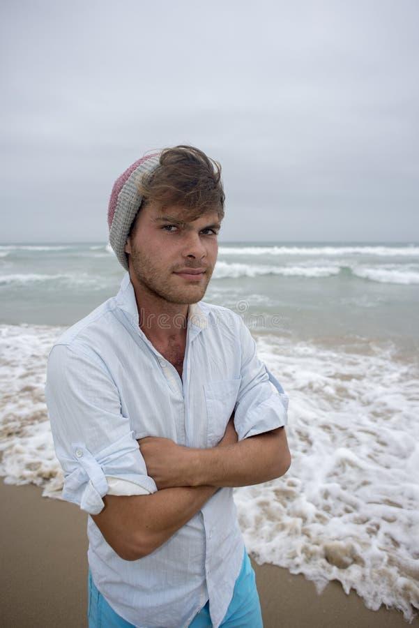 Jonge mens bij strand met beeny op hoofd royalty-vrije stock afbeeldingen
